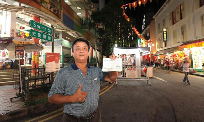 """Mr Ye Wei Qiang posing with one of his tender receipts at the location of the """"lucky"""" stall. He will have a total of five stalls at the bazaar. PHOTO: LIANHE ZAOBAO"""