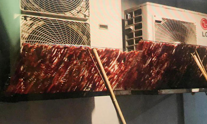 Racks of raw meat being hung to dry outside dusty air-conditioner compressor vents at an HDB block in Beach Road. PHOTO: SHIN MIN DAILY NEWS