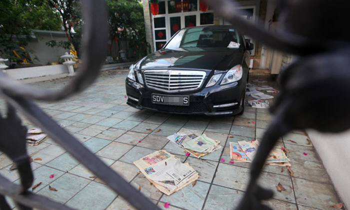 A Mercedes-Benz and a BMW were seen parked at the Tanah Merah semi-detached house of Madam Leong Lai Yee, who was jailed for 14 years for running a ponzi scheme and cheating 53 people of more than $35 million. Photo: Lianhe Zaobao