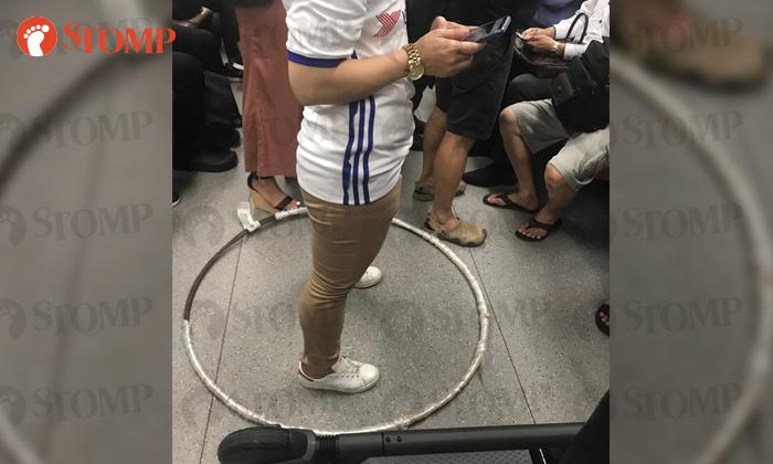 Wanita membuat batas wilayah dengan hula hoop di dalam MRT di Singapura, Kamis (25/7/2019)