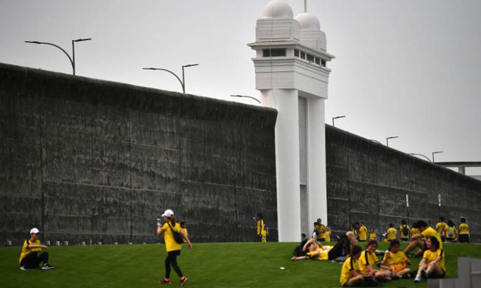 Participants resting and taking photographs outside the old Changi Prison wall at the end of the Yellow Ribbon Prison Run 2019 on Sept 15, 2019. ST PHOTO: LIM YAOHUI