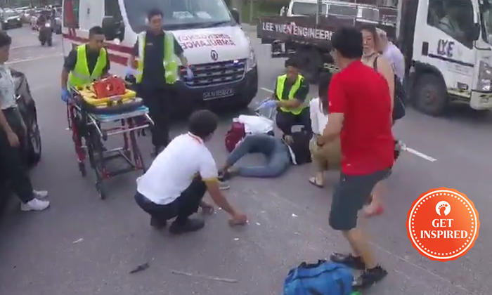 biker and passers by stop to help motorcyclist lying injured on the