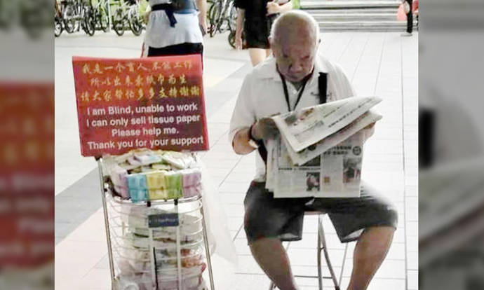 Visually-impaired tissue seller seen reading newspaper in Tampines says he's not a cheat